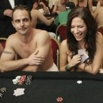 a man and a woman sitting topless on a poker table