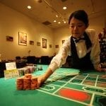 an asian dealer leaning over a casino table