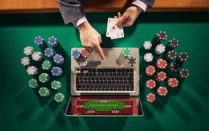a man holding cards and poker chips in front of laptop online casinos