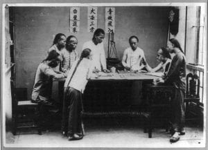 a couple of young men playing fan tan in acient asia, circled around a table