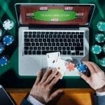 a man playing online poker with real life chips and cards