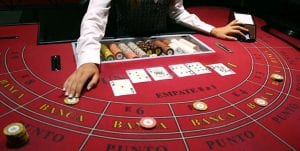 a dealer in casino setting the casino table for baccarat