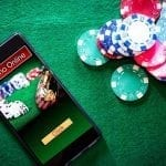 a smartphone next to poker chips laying on a green table