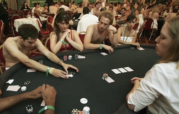 a group of people sitting naked on a poker table