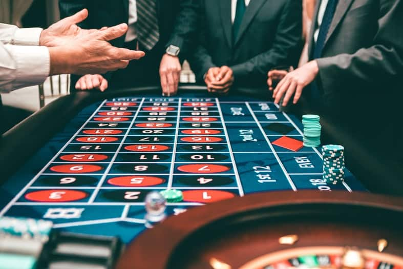 an image with a roulette table and people betting chips with their hands shown