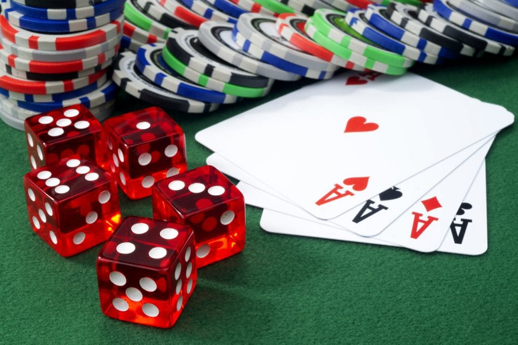 cards and poker chips on a green table