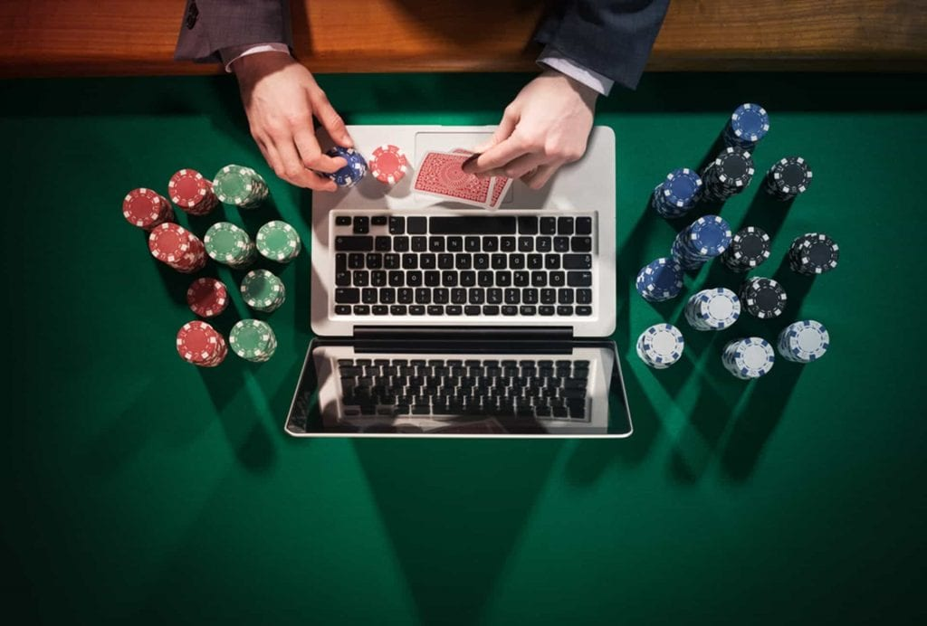 a man holding poker chips in front of his laptop