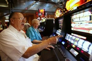 elderl man and a woman playing the slots