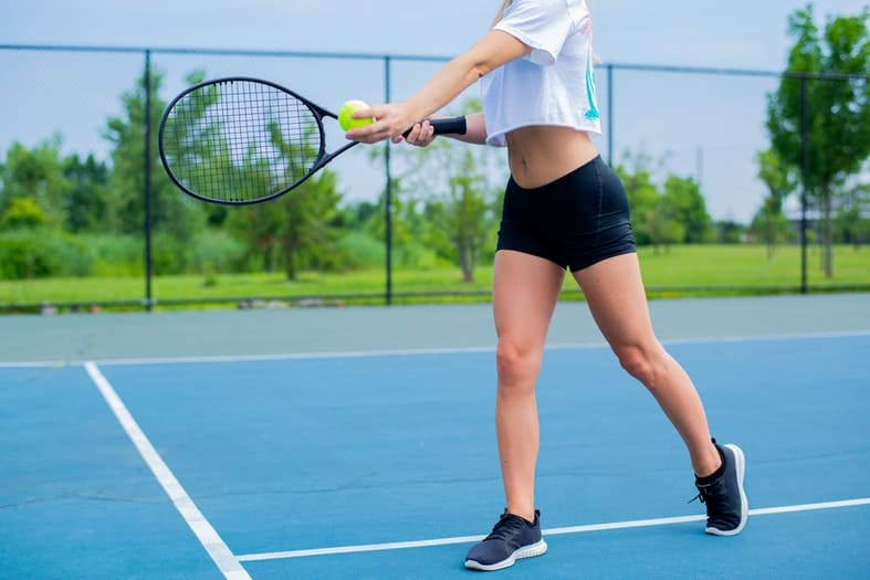 a picture of a woman's body from waist dwon holding a tennis racket with a green ball on a tennis court